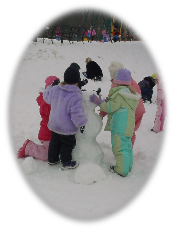 Elementary students building a snowman outside